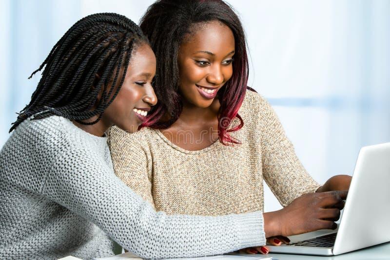Dois estudantes africanos adolescentes que trabalham no portátil fotografia de stock