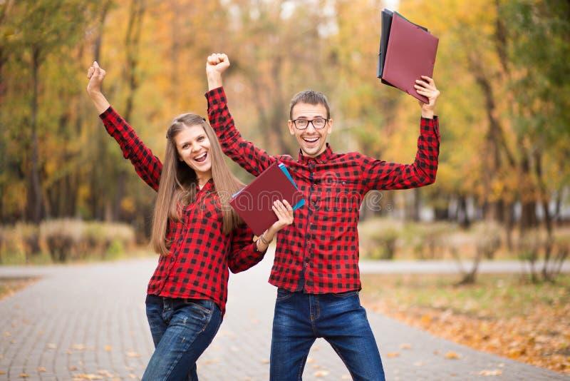 Dois estudantes entusiasmados com mãos acima e exames aprovados no outono imagens de stock
