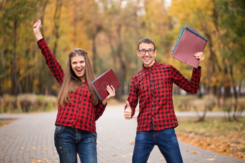 Dois estudantes entusiasmados com mãos acima e exames aprovados no outono fotos de stock