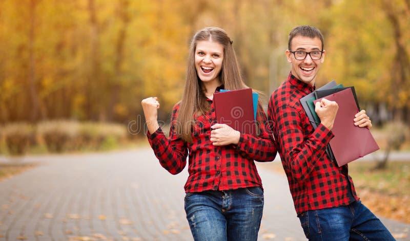 Dois estudantes entusiasmados com m?os acima e exames aprovados no outono foto de stock royalty free
