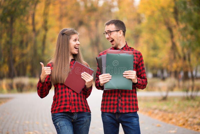 Dois estudantes entusiasmados felizes que aprovaram exames no outono fotos de stock