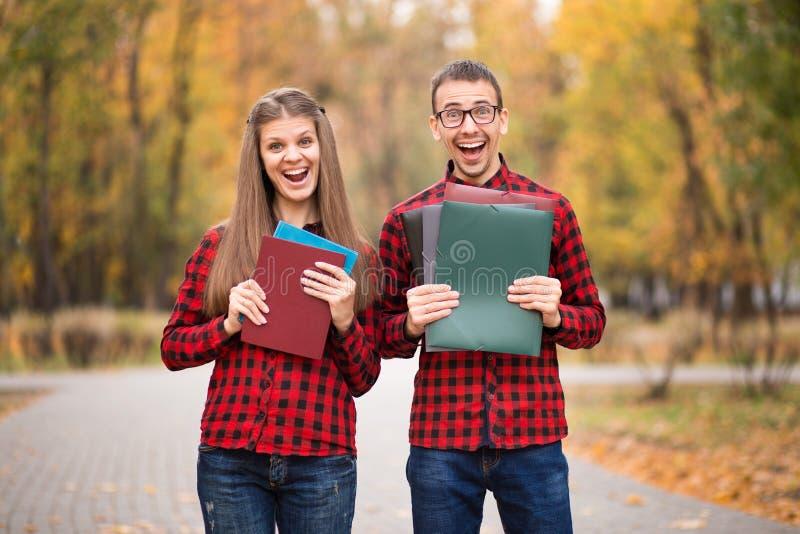 Dois estudantes entusiasmados felizes que aprovaram exames no outono imagens de stock