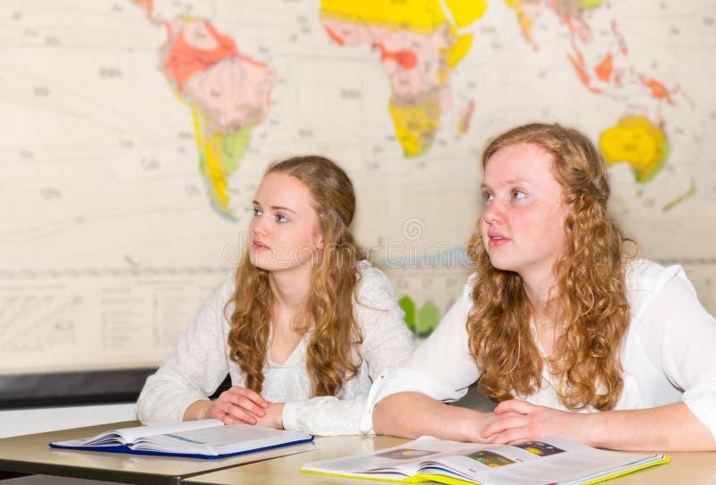 Dois estudantes fêmeas na sala de aula com carta do mundo fotografia de stock royalty free