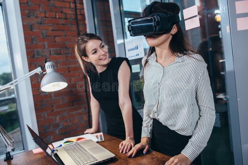 Dois estudantes fêmeas que jogam um jogo 3d nos vidros de VR que têm uma ruptura após uma lição na sala de aula imagem de stock royalty free