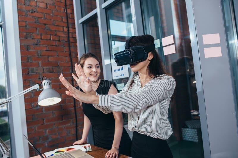 Dois estudantes fêmeas que jogam um jogo 3d nos vidros de VR que têm uma ruptura após uma lição na sala de aula imagens de stock