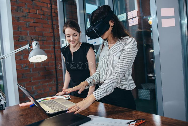 Dois estudantes f?meas que jogam um jogo 3d nos vidros de VR que t?m uma ruptura ap?s uma li??o na sala de aula imagem de stock