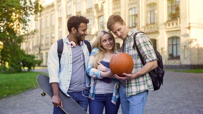 Dois estudantes masculinos que flertam com a menina loura bonita perto da universidade, sentimentos imagem de stock