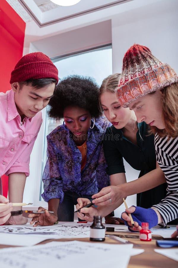 Dois estudantes masculinos que vestem os chapéus que juntam-se a suas amigas imagem de stock