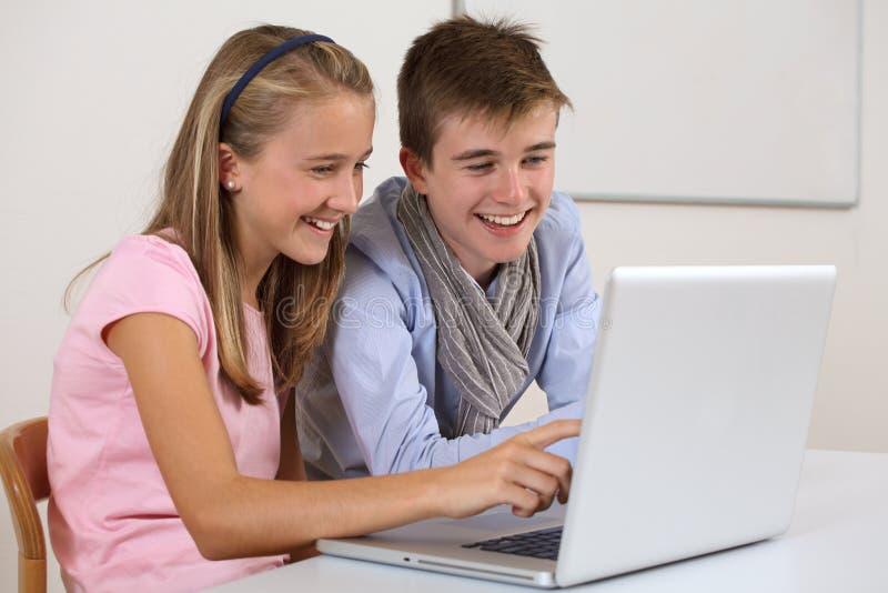 Dois estudantes novos que trabalham em um portátil imagens de stock