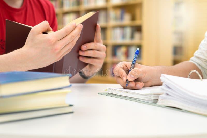 Dois estudantes que estudam, lendo e escrevendo na biblioteca fotografia de stock royalty free