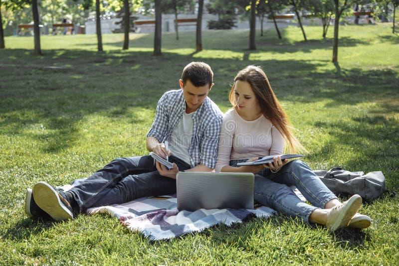 Dois estudantes que preparam-se para o exame com livro de estudo e um portátil que senta-se no gramado Conceito do grupo de estud fotografia de stock royalty free
