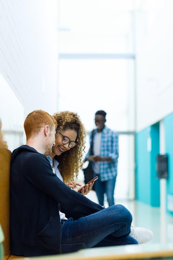 Dois estudantes que usam-se eles telefone celular em uma universidade imagem de stock