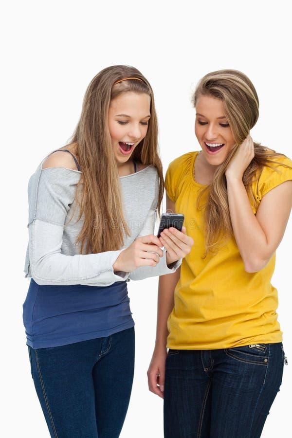 Dois estudantes surpreendidos que olham uma tela do telemóvel imagem de stock royalty free