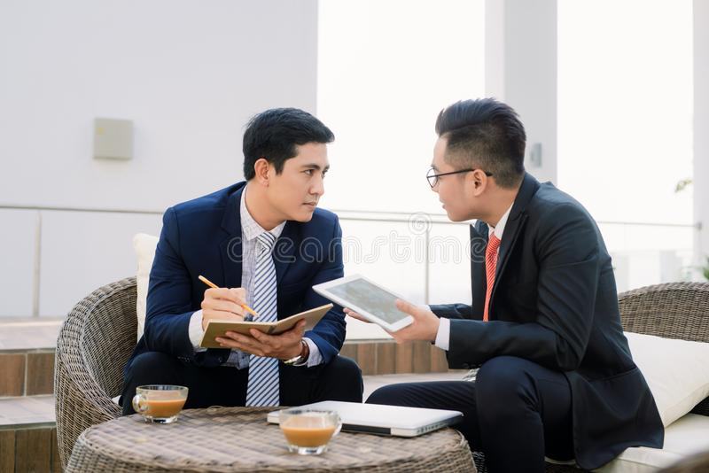 Dois executivos empresariais asiáticos que usam o ipad no parque da cidade imagens de stock royalty free