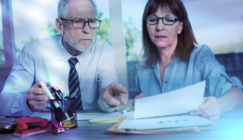 Dois executivos maduros que trabalham junto; efeito da luz imagens de stock royalty free