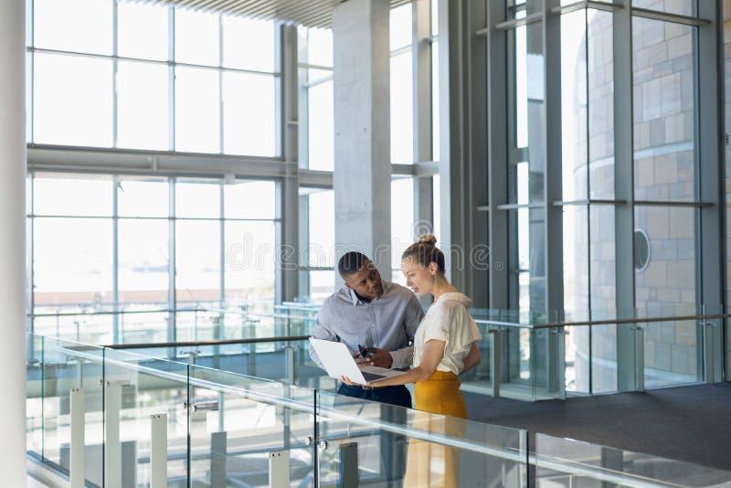 Dois executivos novos estão de trabalho na entrada moderna do escritório imagens de stock
