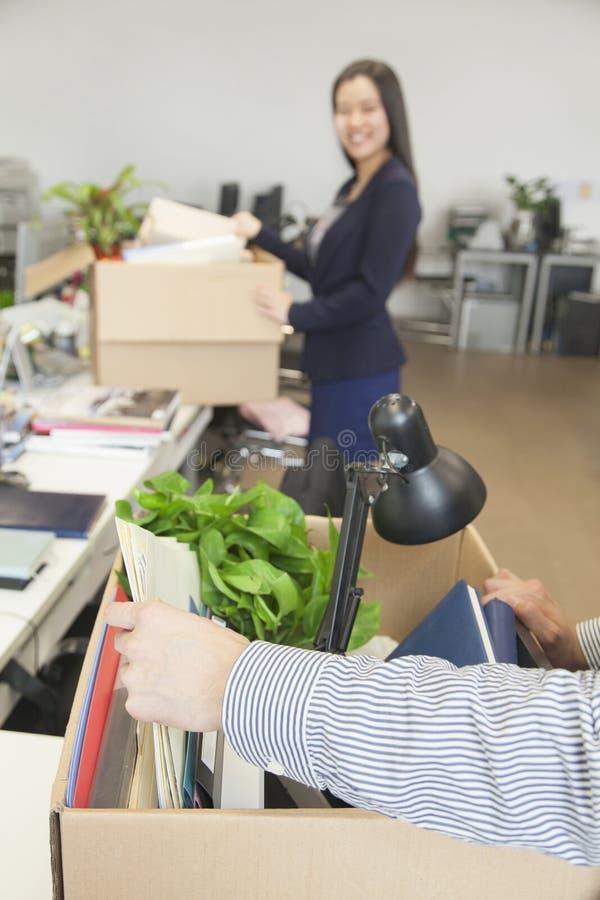 Dois executivos novos que levam caixas com artigos do escritório fotografia de stock