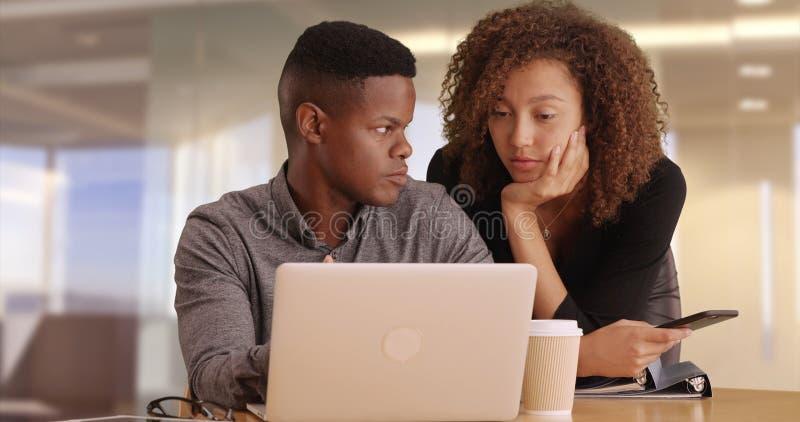 Dois executivos pretos que trabalham em um portátil em um escritório moderno fotos de stock royalty free