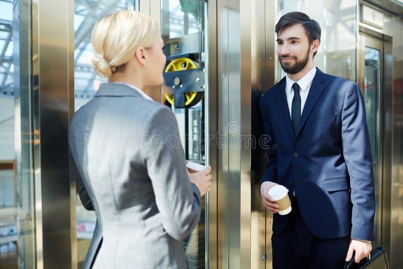 Dois executivos que conversam no elevador fotos de stock royalty free
