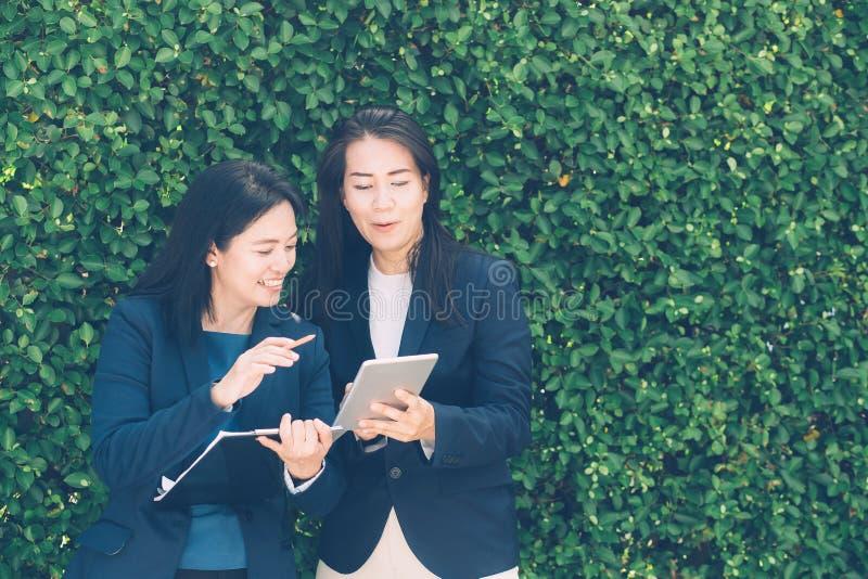 Dois executivos que discutem a informação na tabuleta-e que tomam notas imagem de stock royalty free