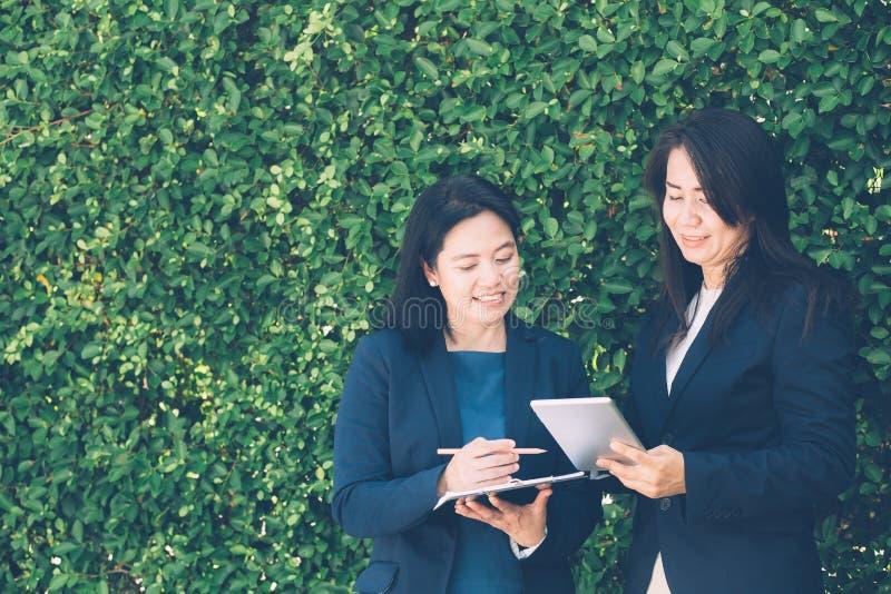Dois executivos que discutem a informação na tabuleta-e que tomam notas como trabalham imagem de stock royalty free