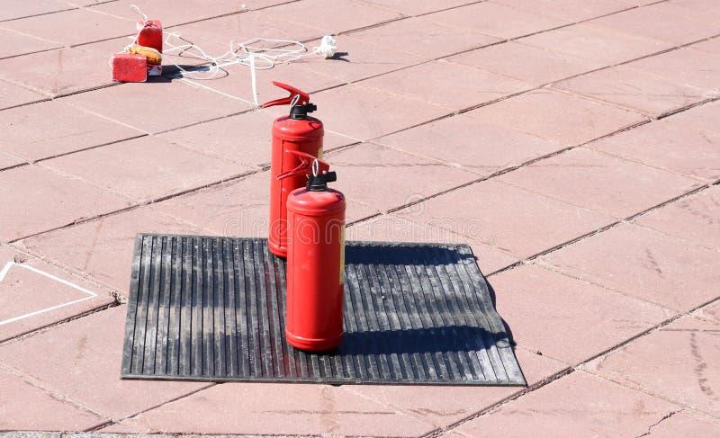 Dois extintores manuais do dióxido ou do pó de carbono do metal vermelho grandes para extinguir um suporte do fogo em uma borrach fotos de stock