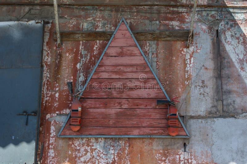 Dois extintores velhos vermelhos penduram em um suporte de madeira triangular imagem de stock royalty free