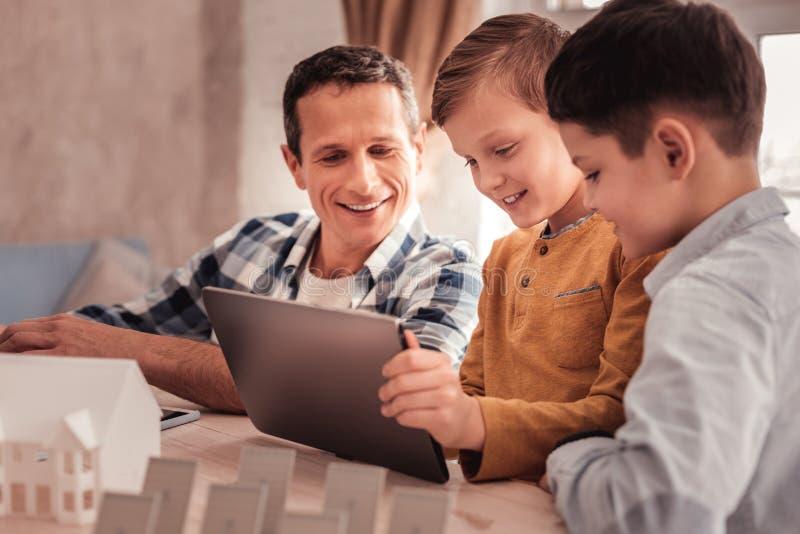 Dois filhos bonitos que mostram suas fotos ao pai adotivo na tabuleta imagem de stock