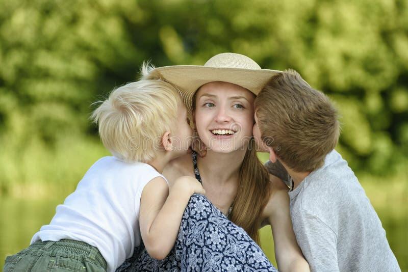 Dois filhos pequenos abraçam a mãe e o beijo no mordente contra o contexto das hortaliças imagem de stock royalty free