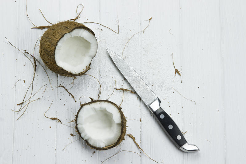 Dois flocos orgânicos brancos marrons tropicais frescos do coco do coco da polpa do coco ordenham a faca no fundo branco de madei imagem de stock