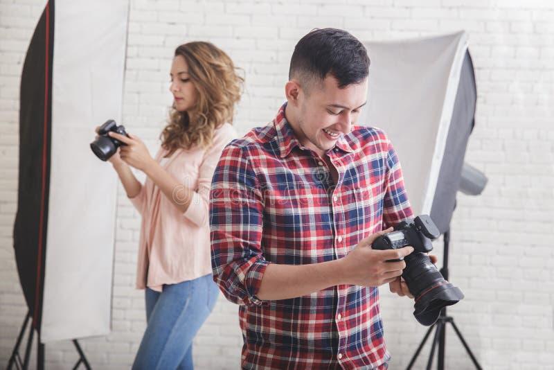 Dois fotógrafo novos no estúdio que verificam sua foto inspecionam i fotografia de stock
