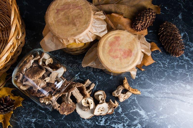 Dois frascos de vidro com os cogumelos selvagens no fundo de mármore preto fotografia de stock royalty free