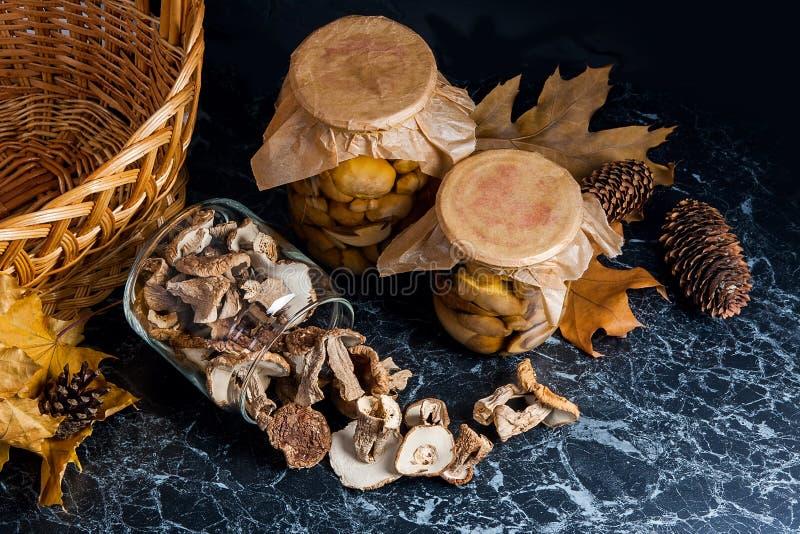 Dois frascos de vidro com os cogumelos selvagens no fundo de mármore preto imagens de stock royalty free