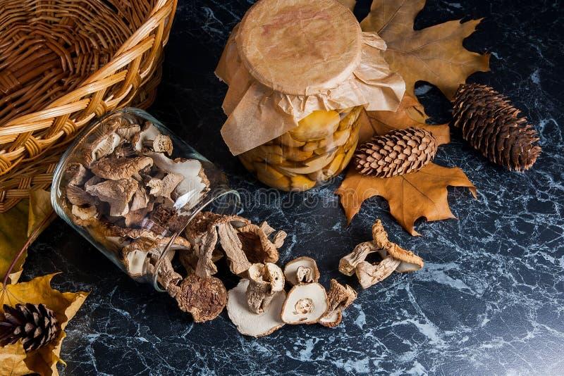 Dois frascos de vidro com os cogumelos selvagens no fundo de mármore preto imagem de stock royalty free