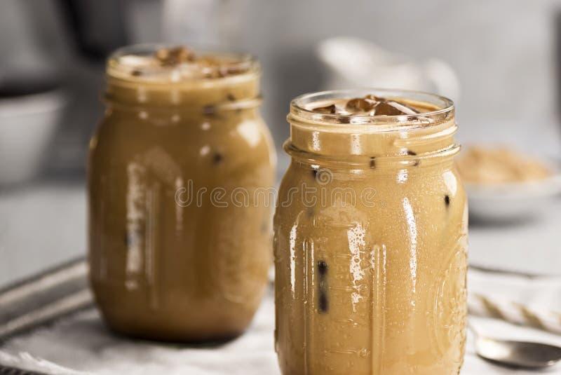 Dois frascos de vidro enchidos com o café congelado com creme imagem de stock
