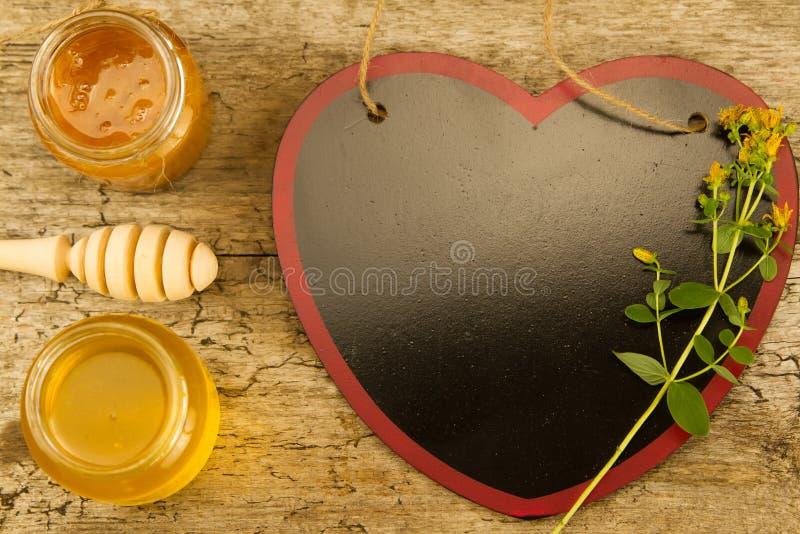 Dois frascos pequenos do mel fresco com drizzler, flores no fundo de madeira imagem de stock royalty free