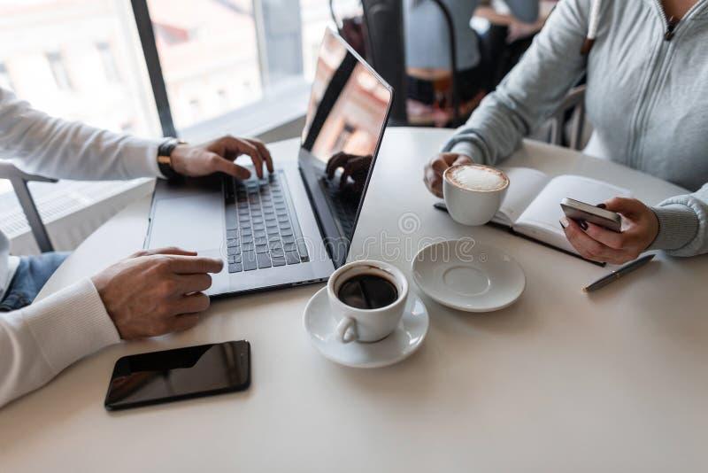 Dois freelancers bem sucedidos que sentam-se nos cafés que trabalham em um projeto criativo para uma xícara de café Close up das  foto de stock