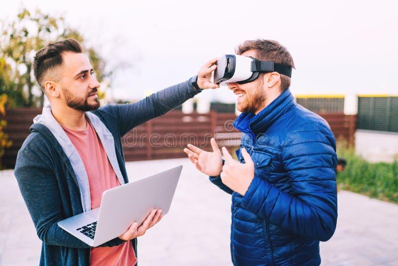 Dois freelancers, colaboradores que têm o divertimento e que trabalham no app novo para óculos de proteção da realidade virtual fotos de stock