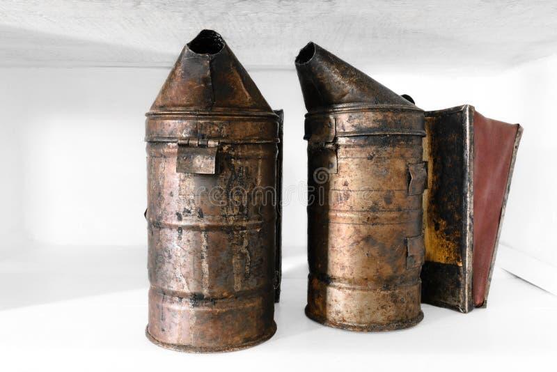 Dois fumadores oxidados, empoeirados e muito idosos da abelha colocados na prateleira branca fotos de stock royalty free