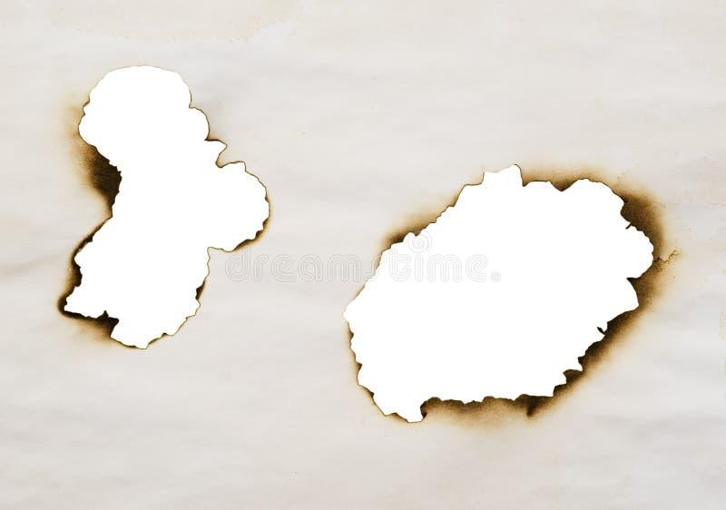 Dois furos queimados fotos de stock