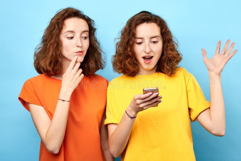Dois gêmeos bonitos sorriso das meninas, olhando o telefone esperto sobre o fundo azul fotos de stock