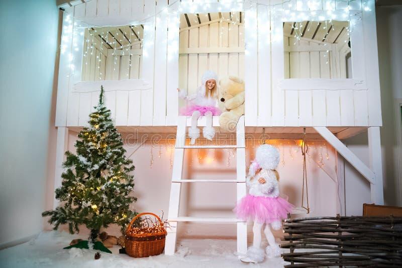 Dois gêmeos das irmãs nos trajes de caniches do cão pelo ano novo As meninas que jogam no patamar de uma casa de madeira branca d foto de stock