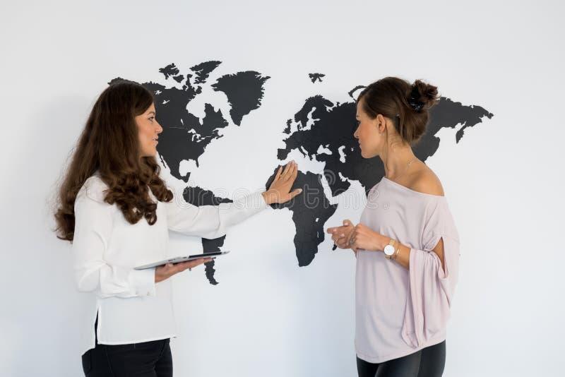 Dois gêmeos das jovens mulheres discutem o negócio fotografia de stock