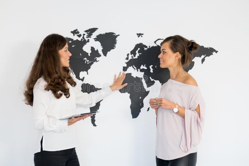 Dois gêmeos das jovens mulheres discutem o negócio imagens de stock