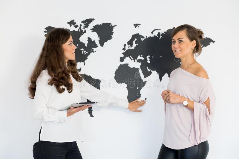 Dois gêmeos das jovens mulheres discutem o negócio fotografia de stock royalty free