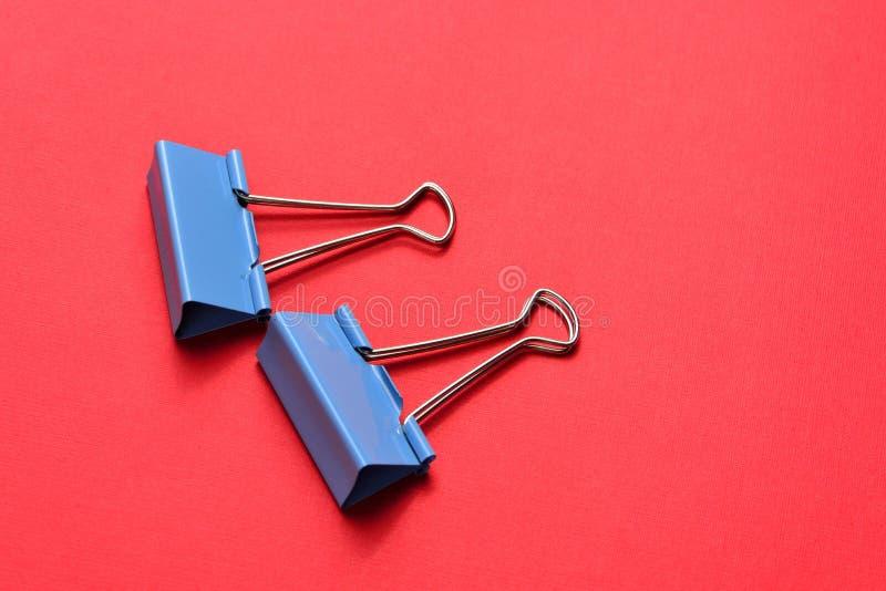 Dois grampos azuis da pasta no fundo vermelho fotos de stock