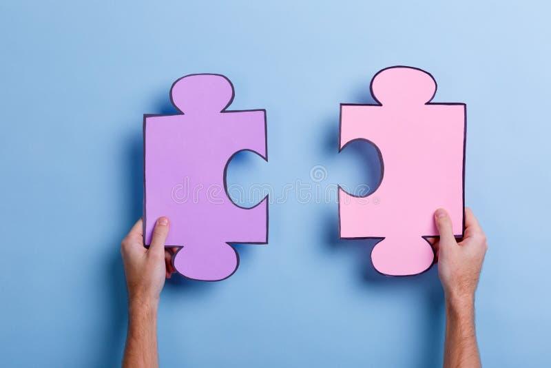 Dois grandes enigmas que guardam as mãos de um homem Em um fundo azul Close-up imagens de stock