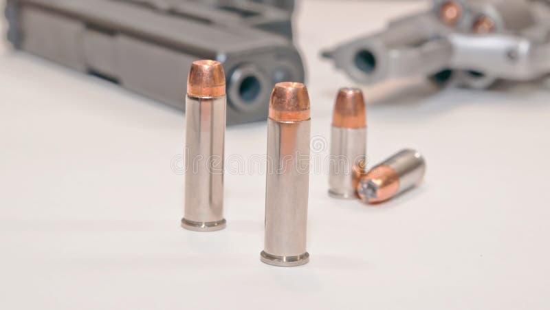 Dois grupos de balas diferentes com um revólver e uma pistola no fundo foto de stock royalty free
