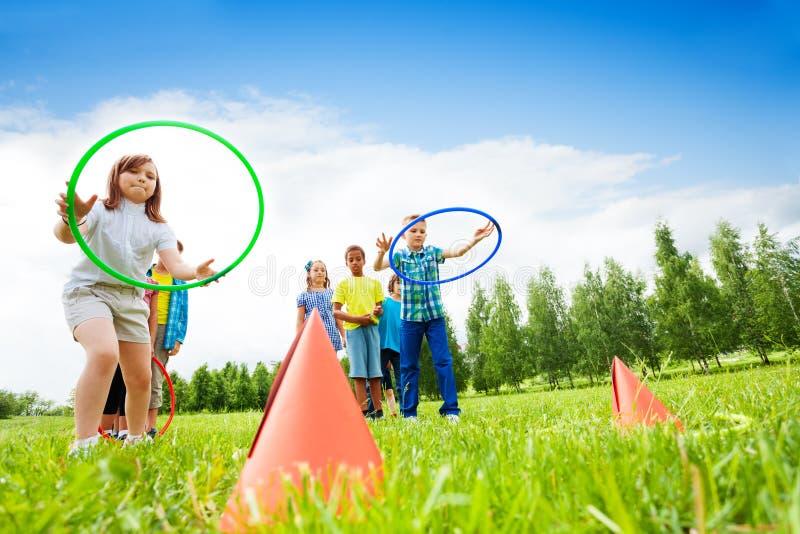Dois grupos de crianças que jogam com aros do hula foto de stock royalty free