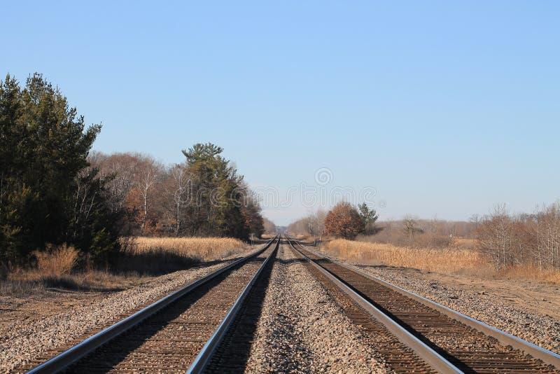 Dois grupos de trilhas de estrada de ferro em um dia agradável da queda fotografia de stock